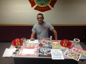 Fireman Sitting with Various Fire Prevention Items